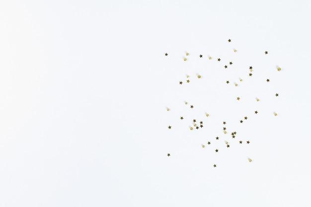 Layout de natal. confete dourado sob a forma das estrelas em um fundo branco. ano novo de 2019