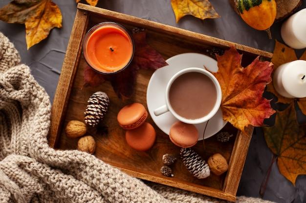 Layout de outono uma xícara de chocolate quente em uma bandeja de madeira com macaroons