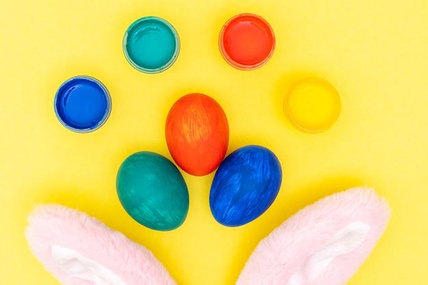 Layout de páscoa com ovos pintados de cores, tintas, orelhas de coelho rosa em fundo amarelo brilhante