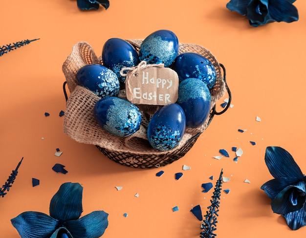 Layout de páscoa criativo feito de ovos coloridos e flores sobre fundo azul. conceito liso leigo da coroa do círculo. o conceito de férias da páscoa.