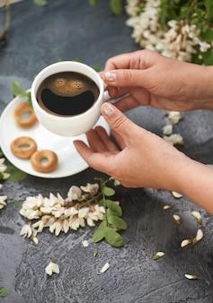 Layout de primavera com café nas mãos femininas e flores de acácia branca.