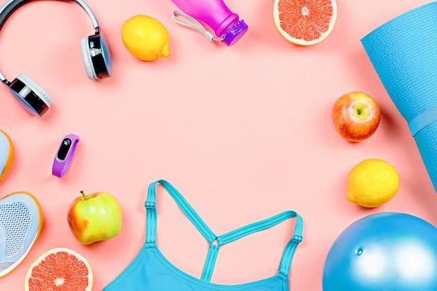 Layout de roupas esportivas e acessórios para mulheres com frutas no fundo rosa.