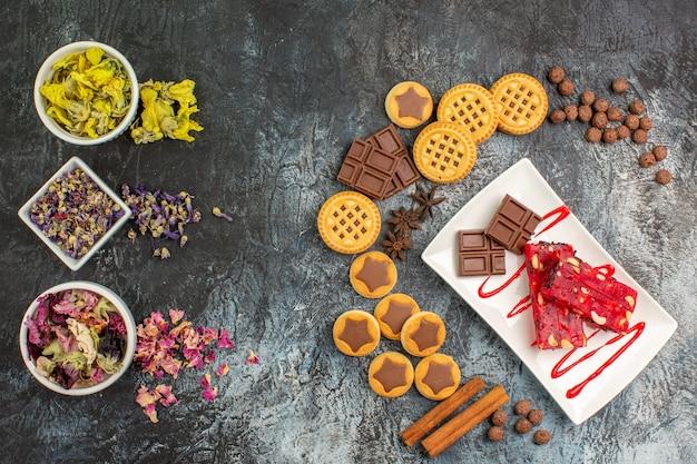 Layout em forma de crescente de doces com um prato de chocolates e tigelas de flores secas em um fundo cinza