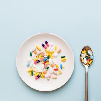 Layout médico criativo feito com comprimidos, cápsulas e suplementos coloridos