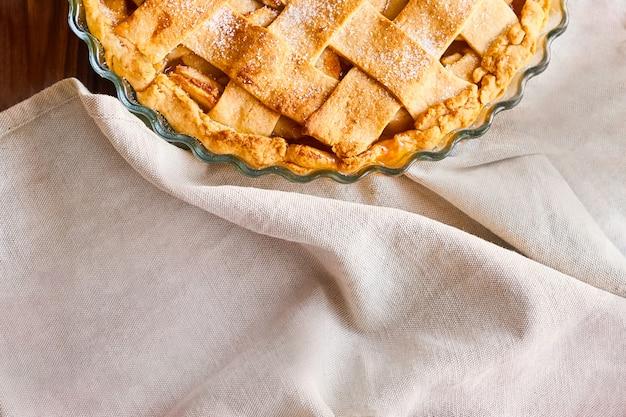 Layout ou natureza morta com torta de maçã caseira em forma de cozinhar na mesa coberta com toalha de mesa leve na cozinha em casa. vista superior com espaço de cópia