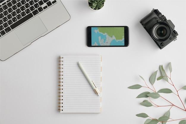 Layout plano de caderno com caneta rodeada de smartphone, fotocâmera, laptop e ramo com folhas verdes