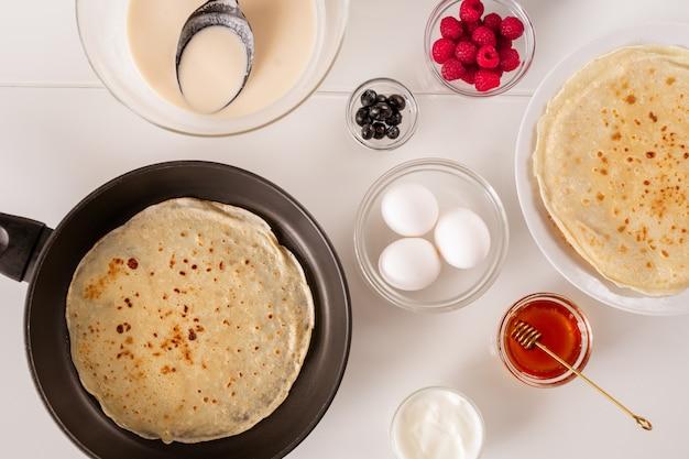 Layout plano de frigideira com panqueca, três ovos frescos em uma tigela, mel, creme de leite, framboesas, amoras e massa líquida na mesa