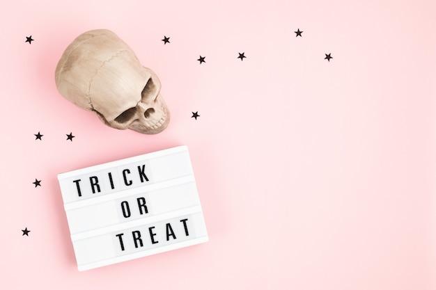 Layout plano de halloween da mesa de luz com texto e decoração de doces ou travessuras
