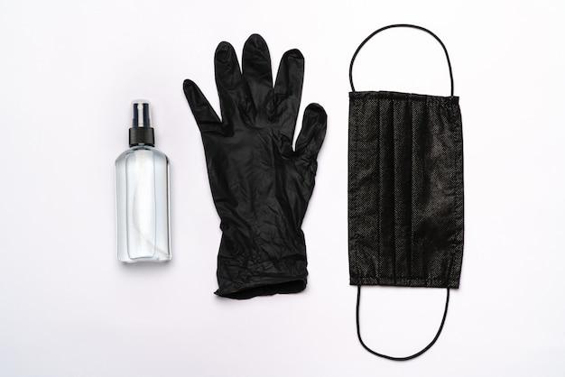 Layout plano de itens de higiene - luvas de látex, máscara e desinfetante para as mãos ou sabonete líquido isolado sobre parede cinza clara.