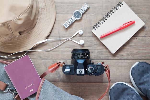 Layout plano de itens de viagem e acessórios com câmera, fones de ouvido em fundo de madeira