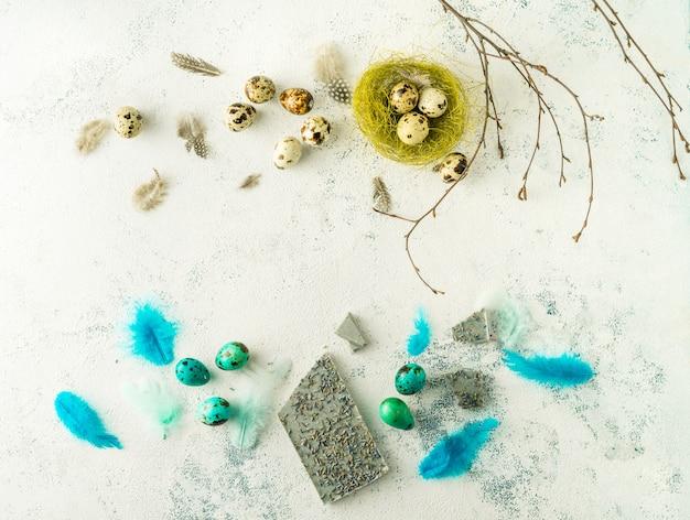 Layout plano de páscoa de ovos de codorna, penas, ninho de pássaro, galhos nus e barra de chocolate