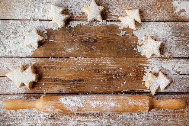 Layout plano sobre uma mesa de madeira com um rolo de madeira e biscoitos em forma de árvores de natal