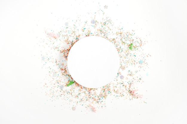 Layout redondo criativo com espaço de cópia feito de confetes coloridos sobre fundo branco. fundo do conceito de celebração. postura plana