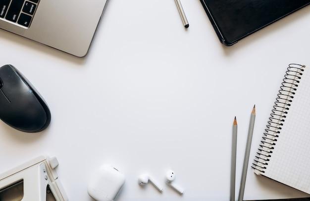 Layout sobre o tema do processo de trabalho ou educação em um fundo branco com bloco de notas, caneta, laptop, mouse de computador, tablet, furador, fones de ouvido, lápis. camada plana, vista superior.