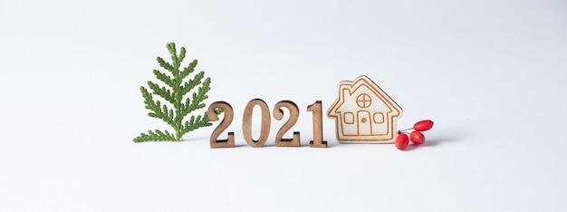 Layouts de ano novo números de madeira 2021 e uma pequena casa próxima. minimalismo. fique em casa conceito.