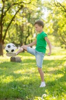 Lazer ativo. garoto loiro concentrado em camiseta verde e shorts recheando bola de futebol no gramado verde