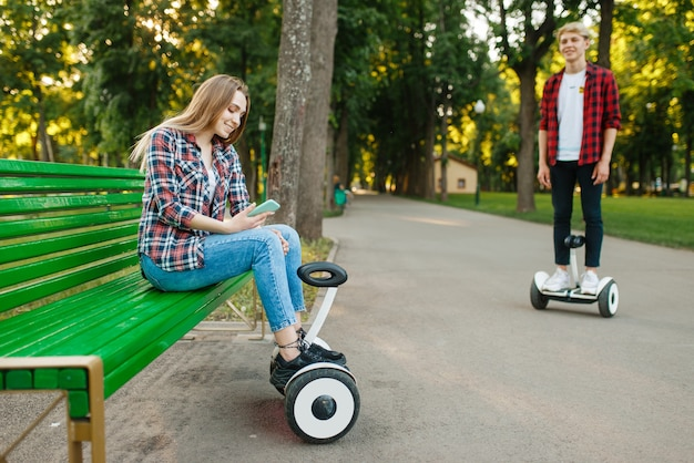 Lazer do jovem casal com placa de giroscópio no parque de verão.