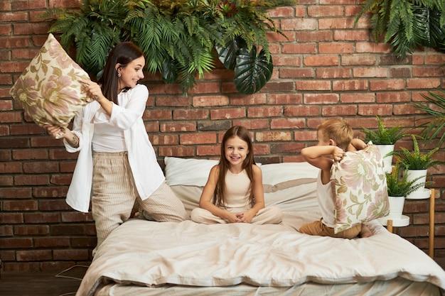 Lazer em família. filha e filho de mãe brigam de travesseiros na cama no quarto. alegria e diversão