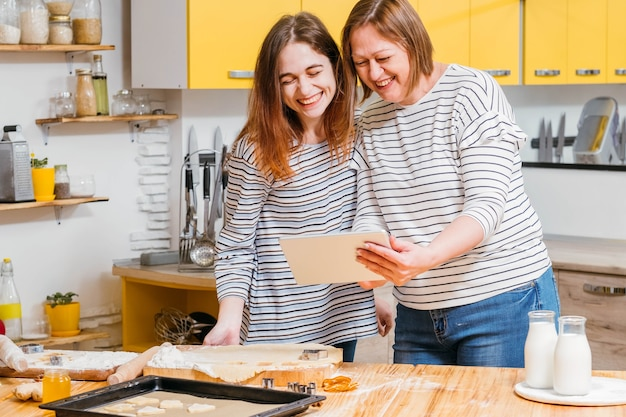 Lazer em família. mãe e filha usando o tablet para assistir a um divertido vídeo tutorial de culinária na cozinha.