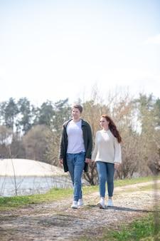 Lazer, estilo de vida. mulher jovem feliz e homem segurando a mão caminhando em um belo lugar ao ar livre em dia ensolarado