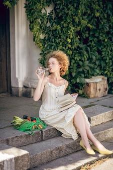 Lazer. mulher jovem sentada na escada com um livro nas mãos
