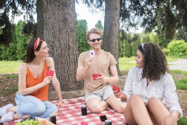 Lazer na natureza. três jovens amigos alegres em roupas casuais jogando cartas, sentados no cobertor sob uma árvore no piquenique