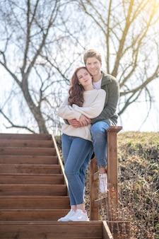 Lazer, natureza. homem sorridente, abraçando uma mulher pensativa em pé na escada, com um humor pensativo positivo na natureza em um dia ensolarado