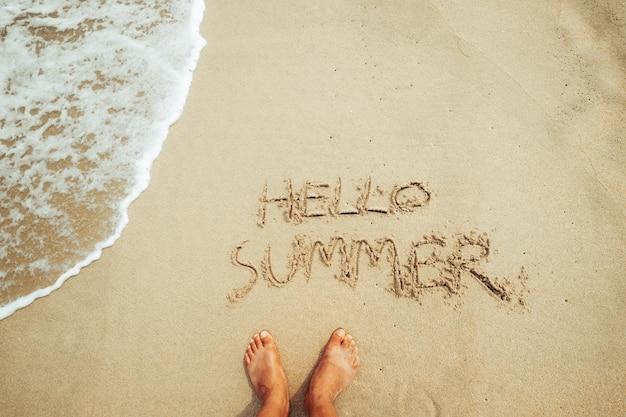 Lazer no verão - pé do homem e texto do olá. verão na areia em uma praia tropical. conceito de férias de verão. tom de cor vintage.