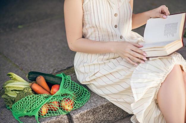 Lazer. uma mulher sentada na escada com um livro nas mãos