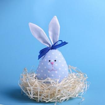 Lebre azul no ninho, cartão de feliz páscoa.