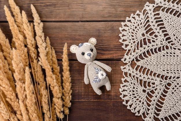 Lebre de brinquedo amarrada com fios de lã em um fundo escuro. trabalho manual, hobby