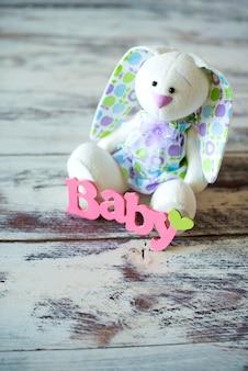 Lebre de brinquedo com o bebê de inscrição em um fundo de madeira.