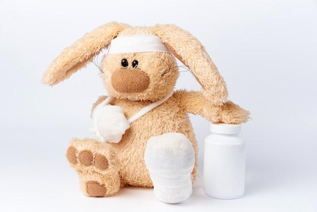 Lebre enfaixado doente bonito com um frasco das medicinas em um fundo branco.