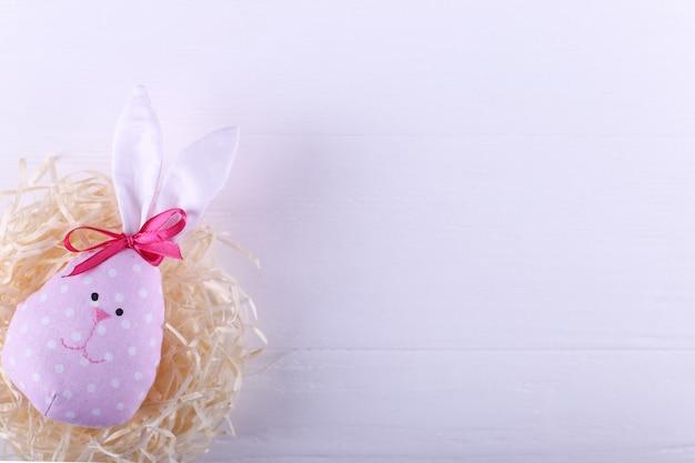Lebre rosa no ninho, cartão de feliz páscoa.