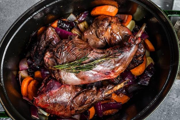 Lebre selvagem com vegetais em molho de vinho branco, panela. carne orgânica. ensopado de cozinha. vista do topo
