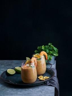 Leche de tigre, peru, equador, comida latino-americana, ceviche de coquetel de peixe cru com limão, limão e coentro. comida tradicional peruana com camarões e chips de banana