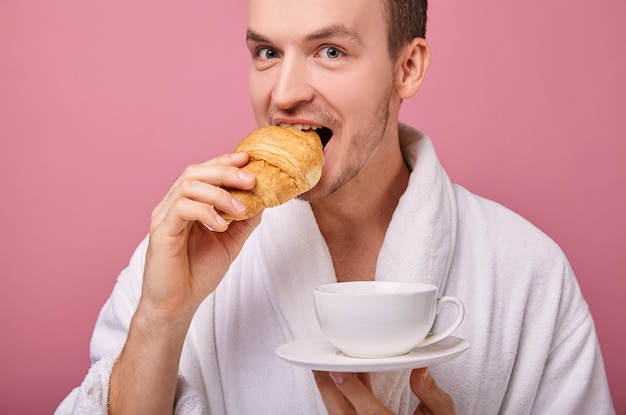 Legal cara bonito em roupão branco comendo croissant perfumado