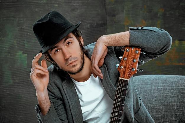 Legal cara sentado com guitarra no espaço cinza