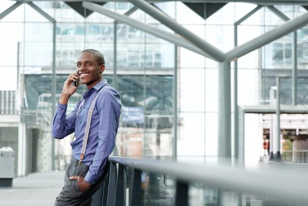 Legal empresário africano sorrindo com celular no edifício