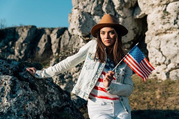 Legal feminino segurando bandeira eua em pé nas rochas