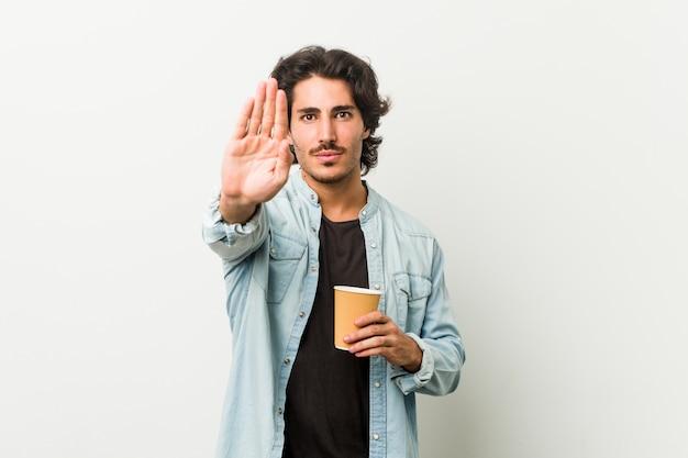 Legal jovem bebendo um café em pé com a mão estendida, mostrando o sinal de stop, impedindo-o.
