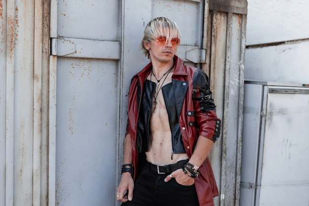 Legal jovem com um torso nu com um penteado elegante em uma jaqueta de couro da moda em óculos de sol vermelhos com jeans fica perto de um antigo prédio de metal cinza ao ar livre.