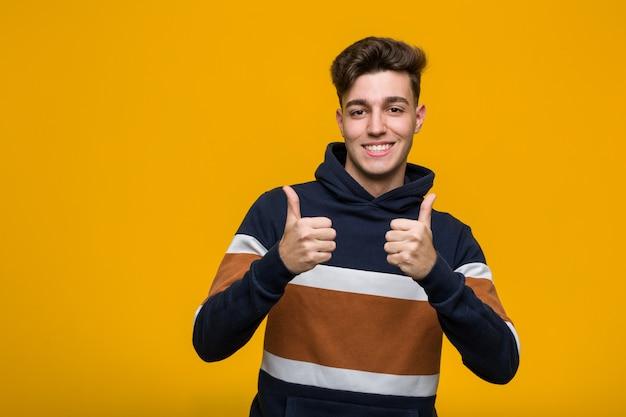 Legal jovem vestindo um capuz, levantando os dois polegares, sorrindo e confiante.