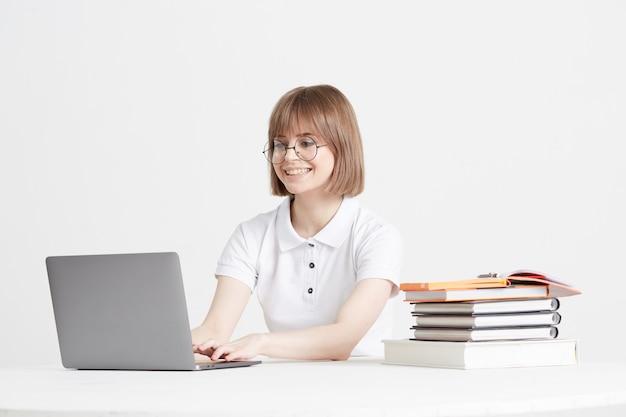 Legal mulher feliz passa por treinamento on-line, sentado em casa. educação escolar remota em um laptop. fique em casa, lições.