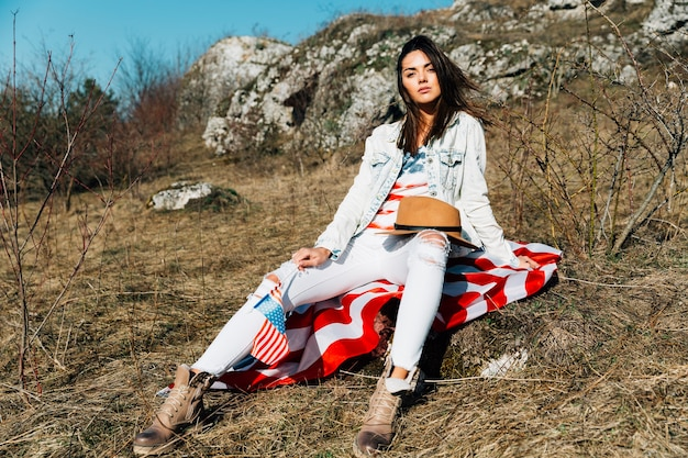 Legal mulher moderna com bandeira americana sentado na natureza