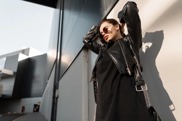 Legal retrato de mulher elegante muamba na moda rock roupas pretas com jaqueta de couro em óculos de sol anda perto de uma parede na cidade à luz do sol. look urbano feminino