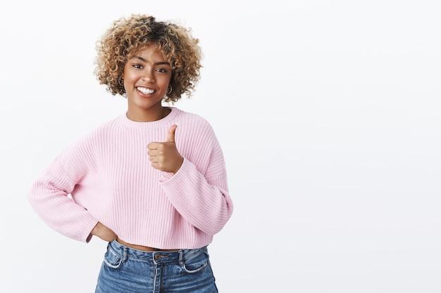 Legal, você fez o melhor. retrato da modelo feminina afro-americana feliz fofa e extrovertida com corte de cabelo loiro, sorrindo alegremente e encantada mostrando o polegar para cima gesto em aprovação a uma boa piada, como