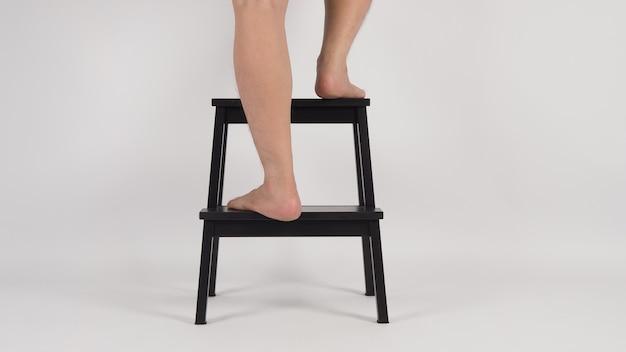 Legs and barefoot é intensificar e virar no banquinho ou escadas de madeira em fundo branco.