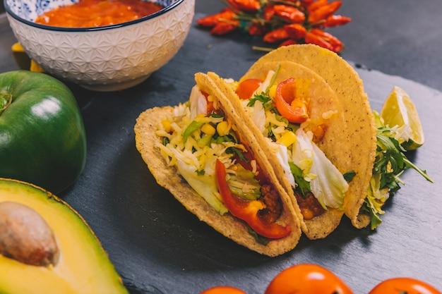 Legumes; abacate com tacos de carne mexicana na ardósia preta