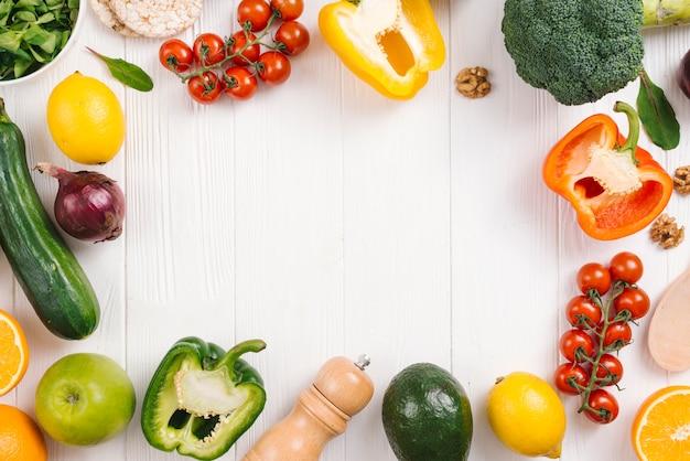 Legumes coloridos frescos; frutas e pimenteiros na mesa de madeira branca